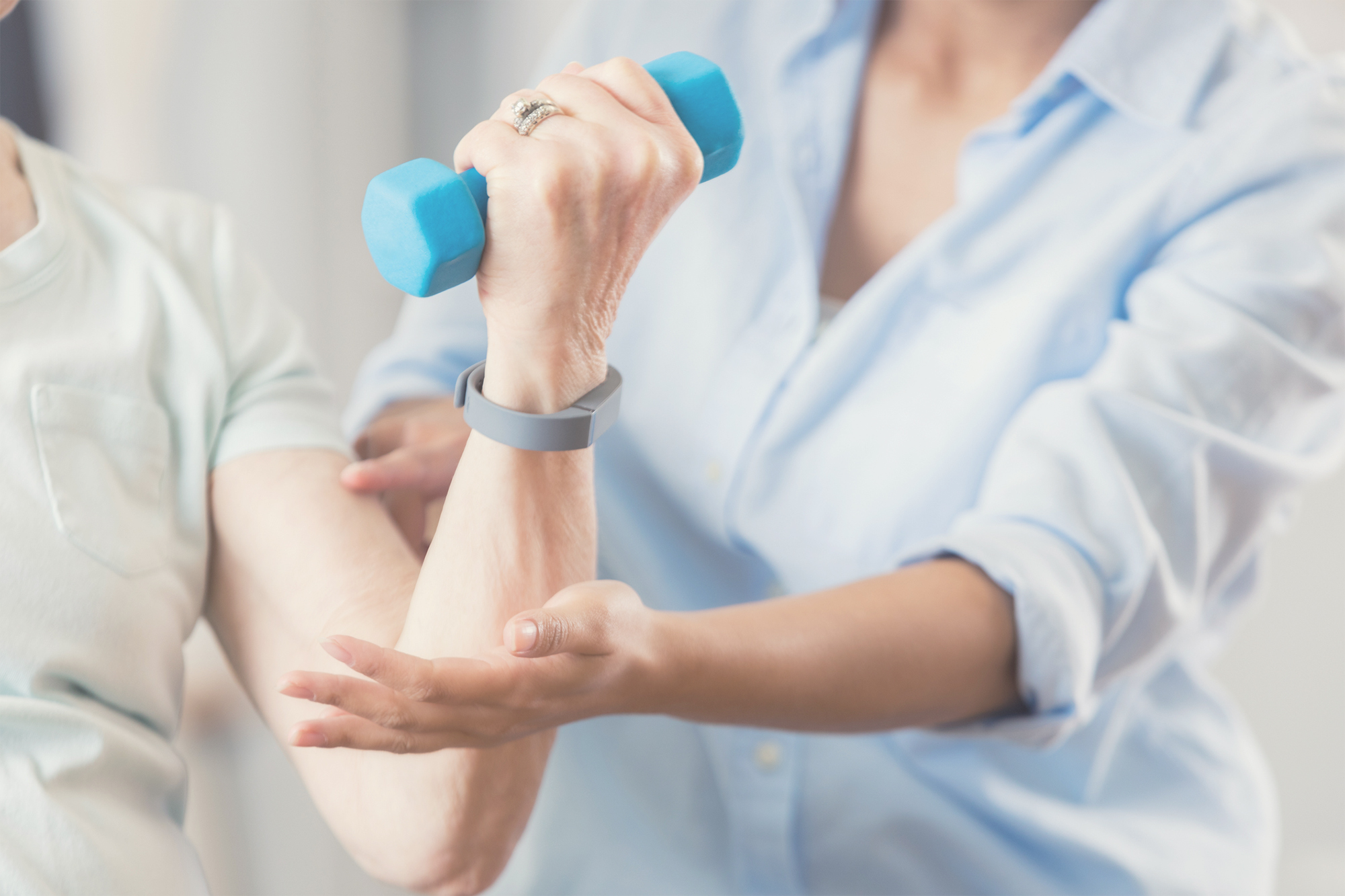 Unrecognizable uses blue hand weight during physical therapy session